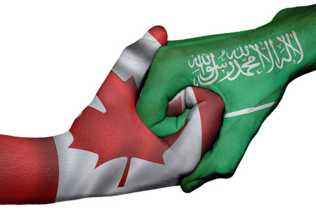 Diplomatic handshake between countries: flags of Canada and Saudi Arabia overprinted the two hands Stock Photo