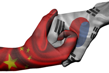 Diplomatic handshake between countries: flags of China and South Korea overprinted the two hands photo