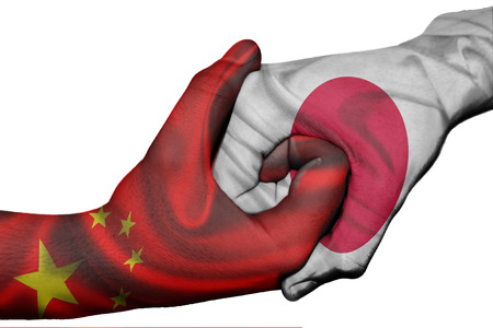 asian business meeting: Diplomatic handshake between countries: flags of China and Japan overprinted the two hands
