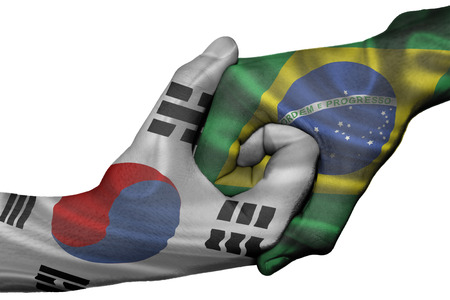 Diplomatic handshake between countries: flags of South Korea and Brazil overprinted the two hands Stock Photo