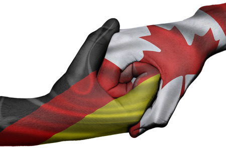 diplomatic: Diplomatic handshake between countries: flags of Germany and Canada overprinted the two hands