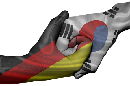 Diplomatic handshake between countries: flags of Germany and South Korea overprinted the two hands photo