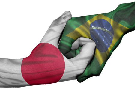 Diplomatic handshake between countries: flags of Japan and Brazil overprinted the two hands photo