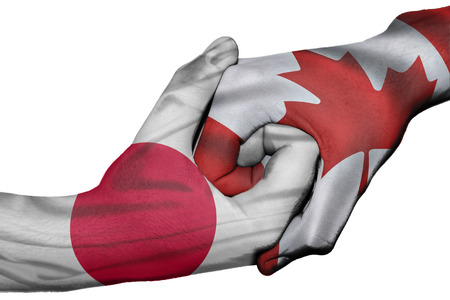 asian business meeting: Diplomatic handshake between countries: flags of Japan and Canada overprinted the two hands Stock Photo