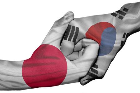 bandera japon: Apretón de manos diplomática entre países: las banderas de Japón y Corea del Sur sobreimpresas las dos manos