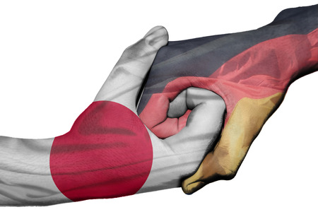 Diplomatic handshake between countries: flags of Japan and Germany overprinted the two hands photo