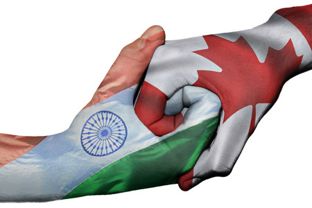 diplomatic: Diplomatic handshake between countries: flags of India and Canada overprinted the two hands