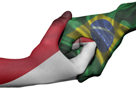Diplomatic handshake between countries: flags of Indonesia and Brazil overprinted the two hands photo