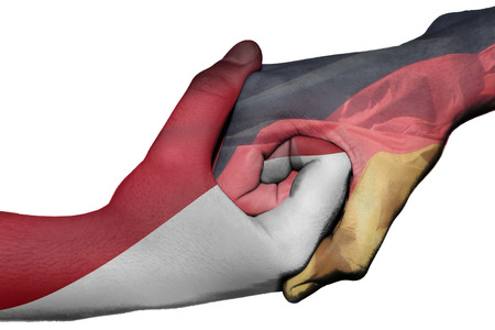 Diplomatic handshake between countries: flags of Indonesia and Germany overprinted the two hands photo