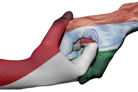 Diplomatic handshake between countries: flags of Indonesia and India overprinted the two hands photo
