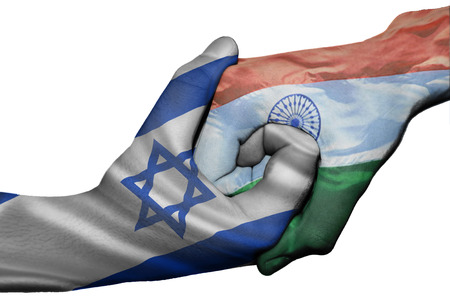 Diplomatic handshake between countries: flags of Israel and India overprinted the two hands photo