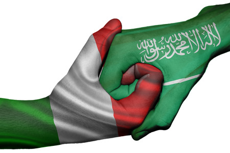 Diplomatic handshake between countries: flags of Italy and Saudi Arabia overprinted the two hands