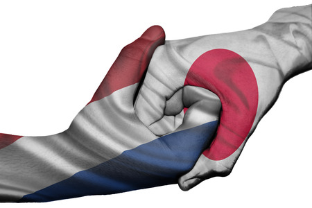 Diplomatic handshake between countries: flags of Netherlands and Japan overprinted the two hands photo