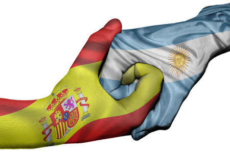 Diplomatic handshake between countries: flags of Spain and Argentina overprinted the two hands Stock Photo