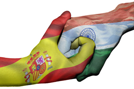 Diplomatic handshake between countries: flags of Spain and India overprinted the two hands photo