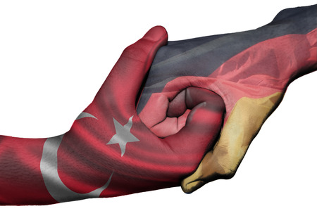Diplomatic handshake between countries: flags of Turkey and Germany overprinted the two hands