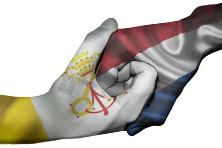 Diplomatic handshake between countries: flags of Vatican City and Netherlands overprinted the two hands photo