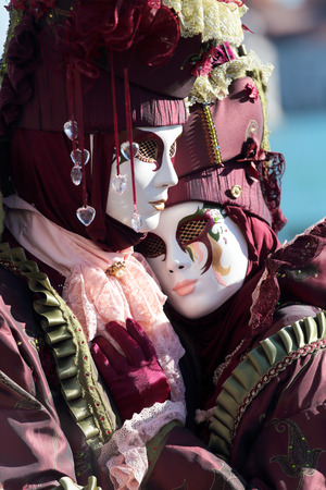 painted face mask: A masked hugging couple exhibited during the traditional festival of Carnival of Venice, Italy (2014 edition) Stock Photo