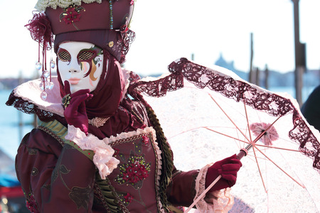 painted face mask: A red masked lady with parasol umbrella exhibited during the traditional festival of Carnival of Venice, Italy (2014 edition)