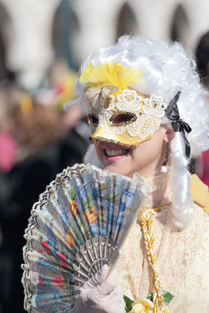 enigma: VENICE, ITALY - February 23: An unidentified young woman with a fan is masked during the traditional festival of Carnival on February 23, 2014 in Venice, Italy