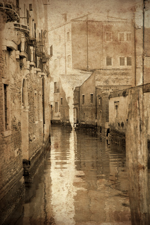 Retro and vintage styled view of channels of the romantic city of Venice, Italy. Grunge texture applied as background photo