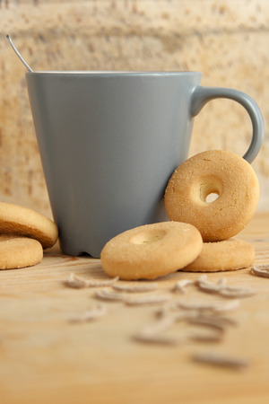 A mug of milk with round biscuits and bran sticks on a wooden background Stock Photo