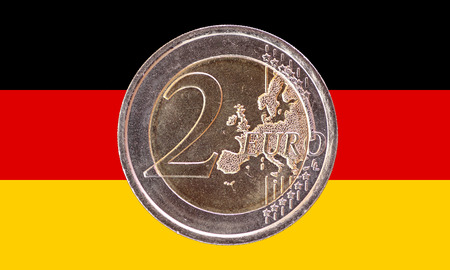 Common face of two euros coin isolated on the national flag of Germany as background