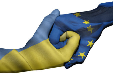 diplomatic: Diplomatic handshake between countries: flags of Ukraine and European Union overprinted the two hands Stock Photo