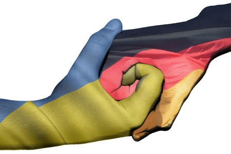 Diplomatic handshake between countries: flags of Ukraine and Germany overprinted the two hands photo