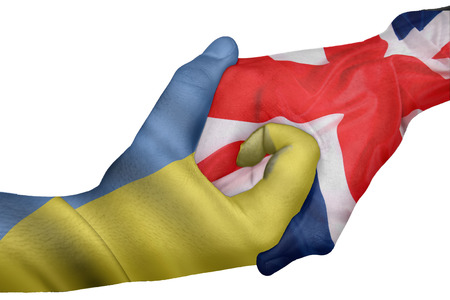 diplomatic: Diplomatic handshake between countries: flags of Ukraine and United Kingdom overprinted the two hands