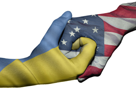 diplomatic: Diplomatic handshake between countries: flags of Ukraine and United States overprinted the two hands