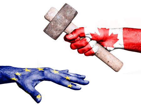 Flag of Canada overprinted on a hand holding a heavy hammer hitting a hand representing the European Union. Conceptual image for political, fiscal or social aggressions, penalties, taxation