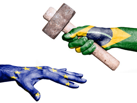 fiscal: Flag of Brazil overprinted on a hand holding a heavy hammer hitting a hand representing the European Union. Conceptual image for political, fiscal or social aggressions, penalties, taxation