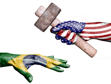 fiscal: Flag of United States overprinted on a hand holding a heavy hammer hitting a hand representing the Brazil. Conceptual image for political, fiscal or social aggressions, penalties, taxation