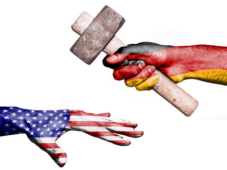 fiscal: Flag of Germany overprinted on a hand holding a heavy hammer hitting a hand representing the United States. Conceptual image for political, fiscal or social aggressions, penalties, taxation