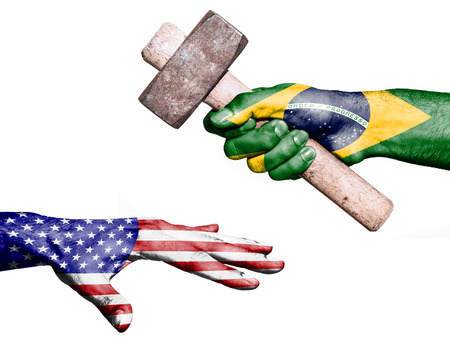 maul: Flag of Brazil overprinted on a hand holding a heavy hammer hitting a hand representing the United States. Conceptual image for political, fiscal or social aggressions, penalties, taxation