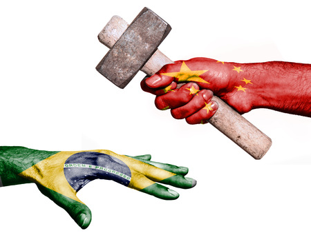 fiscal: Flag of China overprinted on a hand holding a heavy hammer hitting a hand representing the Brazil. Conceptual image for political, fiscal or social aggressions, penalties, taxation