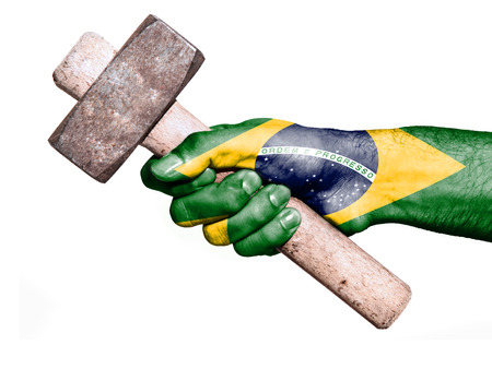 work workman: National flag of Brazil overprinted the hand of a man handling a heavy hammer isolated on a white background. Conceptual image for work, job, workman