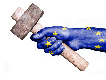 work workman: National flag of European Union overprinted the hand of a man handling a heavy hammer isolated on a white background. Conceptual image for work, job, workman