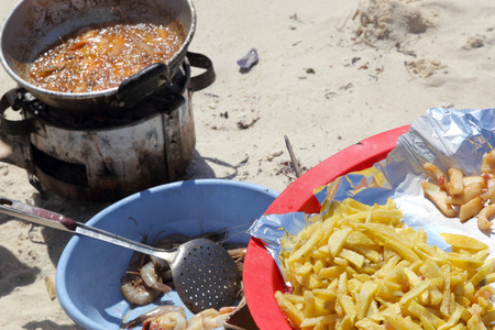 accompaniment: A pan of hot oil with shrimps frying on the beach with fries as accompaniment