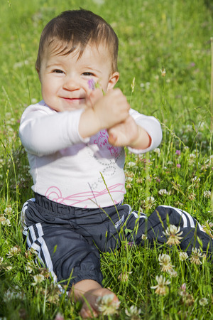 six months: A six months old baby girl sitting on a lawn and showing a flower in her hands Stock Photo