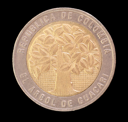 issued: Head face of a 500 pesos coin, issued by the Republic of Colombia in 2000. This coin depicts the holy tree of Guacari for celebrating the Guacari inhabitants who preserve the nature and environment. Image isolated on black background
