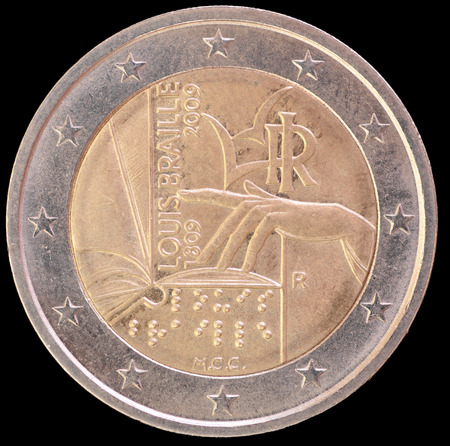 circulated: A commemorative circulated two euro coin issued by Italy in 2009 and depicting a hand reading an open book by touch to celebrate the 200th anniversary of Louis Braille's birth. Image isolated on black background.