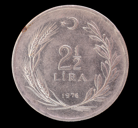 issued: Two and half old turkish lira coin, issued from Turkey in 1976. This currency has been one of worlds least valuable currency. Image isolated on black background