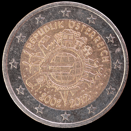 circulated: A commemorative circulated two euro coin issued by Austria in 2012 and celebrating the ten years of the Euro. Image isolated on black background. Stock Photo
