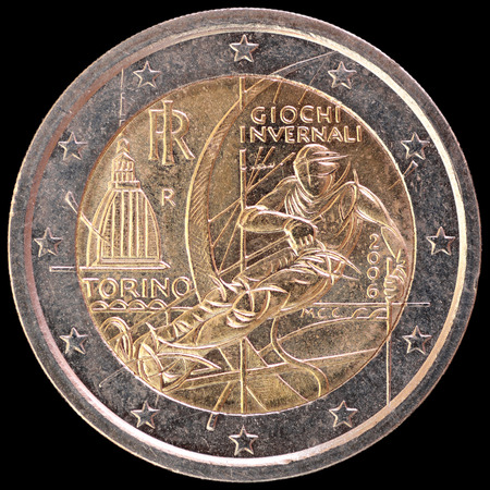 circulated: A commemorative circulated two euro coin issued by Italy in 2006 depicting a skier to celebrate the Olympic Winter Games of Turin. Image isolated on black background.