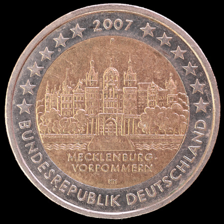 circulated: A commemorative circulated two euro coin issued by Germany in 2007 to celebrate depicting the Schwerin Castle located in the federal state of Mecklenburg-West Pomerania. Image isolated on black background.
