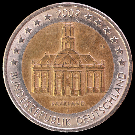 circulated: A commemorative circulated two euro coin issued by Germany in 2009 showing the Ludwigskirche, a symbol of Saarbrucken, the capital of the federal state of Saarland. Image isolated on black background.