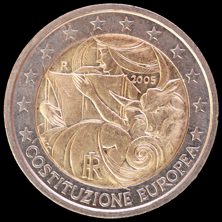 circulated: A commemorative circulated two euro coin issued by Italy in 2005 to celebrate the 1st anniversary of the signing of the European Constitution. Image isolated on black background. Stock Photo