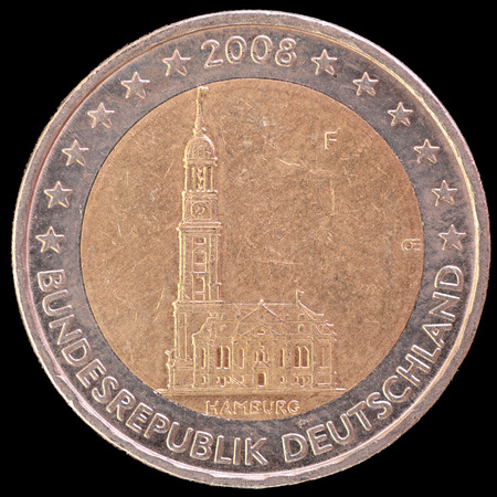 circulated: A commemorative circulated two euro coin issued by Germany in 2008 depicting the baroque church of St. Michaelis located in the federal state of Hamburg. Image isolated on black background.